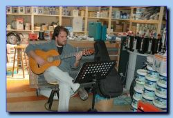 Panayotis Amirsonis is playing guitar in his ironmonger-shop.